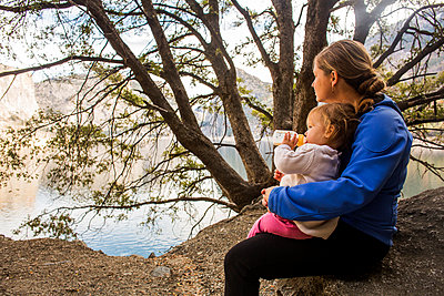 Caucasian mother and daughter sitting at lake - p555m1306384 by Adam Hester