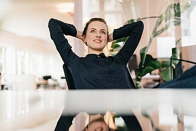 Junge Geschäftsfrau im Büro träumt vor sich hin - p586m1451940 von Kniel Synnatzschke