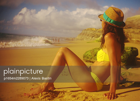 Young woman sitting on a beach - p1654m2289073 by Alexis Bastin
