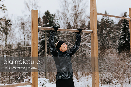 Smiling woman exercising at winter - p312m2299700 by Plattform