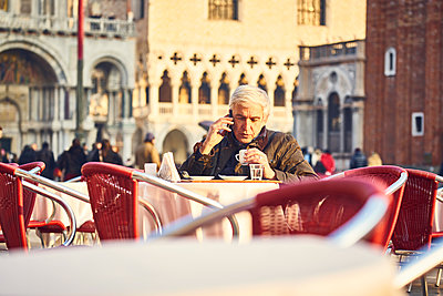 Man phoning in a sidewalk cafe on St. Mark's Square - p1312m2082203 by Axel Killian