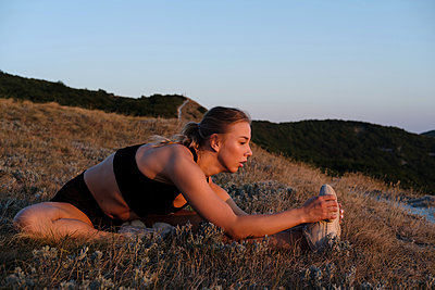 Athletic young woman is stretching and training outdoor on grass - p1363m2013485 by Valery Skurydin