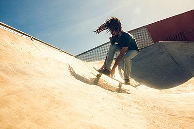 Young man with dreadlocks skateboarding in a skatepark - p300m1120826f by Kiko Jimenez