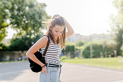 Portrait of smiling young woman with backpack outdoors in summer - p300m2029161 by Giorgio Fochesato
