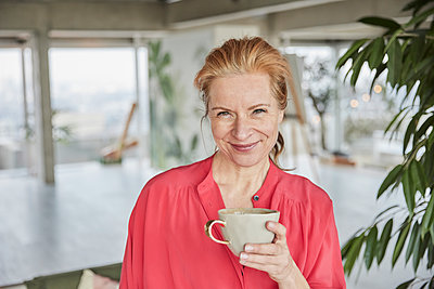 Smiling mature woman holding coffee cup at home - p300m2266072 by Jo Kirchherr