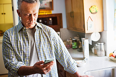 Senior man standing in a kitchen, using a mobile phone. - p1100m1177501 by Mint Images