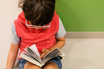 Boy with eyeglasses sitting on the floor reading a book - p1166m2094643 by Cavan Images