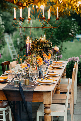 Festive laid table with candles outdoors - p300m2059832 by Alberto Bogo