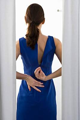 A woman trying on a dress - p3018895f by Paul Hudson