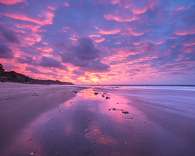 Intensely coloured and mirrored dawn sky looking towards Orcombe Point, Exmouth, Devon, England, United Kingdom - p871m2113759 by Baxter Bradford