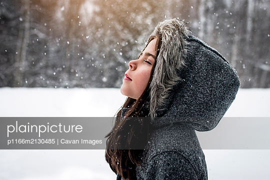 girl stands peacefully outdoors while catching snowflakes on snow day - p1166m2130485 by Cavan Images