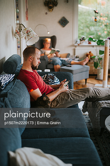 Mother and son chilling out in the living room - p1507m2220173 by Emma Grann