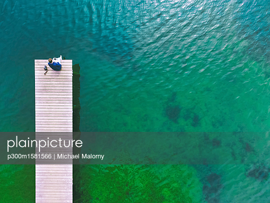 Germany, Bavaria, Chiemsee, man sitting on jetty - p300m1581566 von Michael Malorny