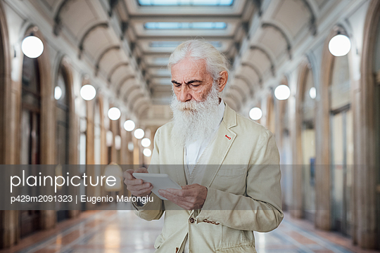 Senior businessman using digital tablet inside office building, Milano, Lombardia, Italy - p429m2091323 by Eugenio Marongiu