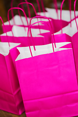 Close up of bright pink paper bags. - p1100m1544323 by Mint Images