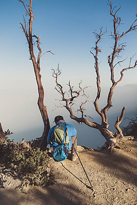 Young man looking at Ijen lake - p1166m2137441 by Cavan Images