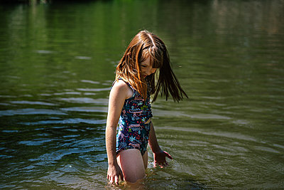 Portrait of a young happy girl playing in a river on a sunny day - p1166m2233043 by Cavan Images