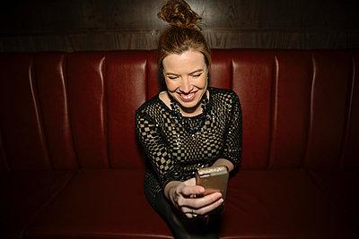Laughing, happy female millennial taking selfie in nightclub - p1192m1583692 by Hero Images