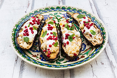 Filled aubergines with couscous, yogurt sauce, mint and pomegranate seeds - p300m2004702 von Larissa Veronesi