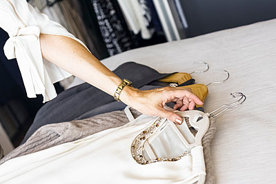 Arm of Caucasian woman placing clothing on bed - p555m1523022 by Julien McRoberts