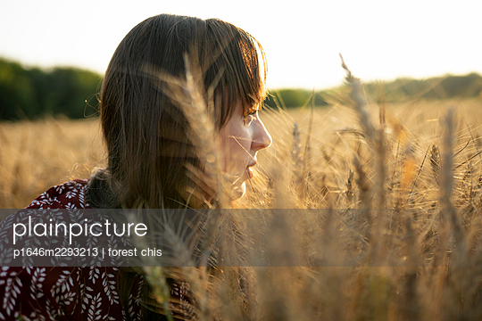 Young woman in a cornfield - p1646m2293213 by Slava Chistyakov