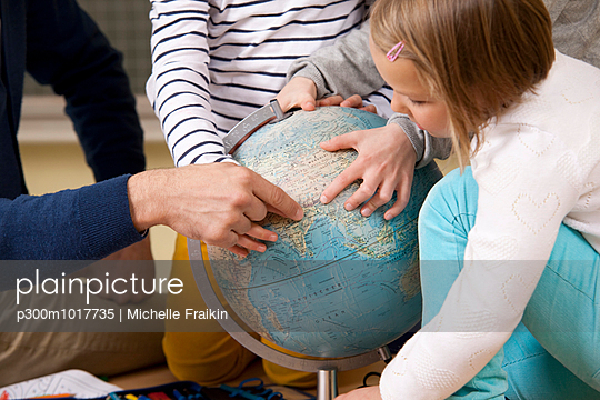 Teacher and pupils pointing at globe in classroom