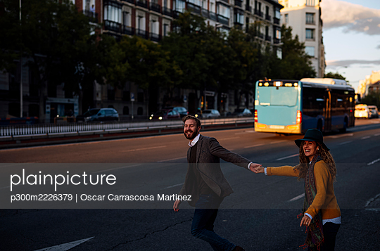 Couple holding hands while crossing road in city - p300m2226379 by Oscar Carrascosa Martinez
