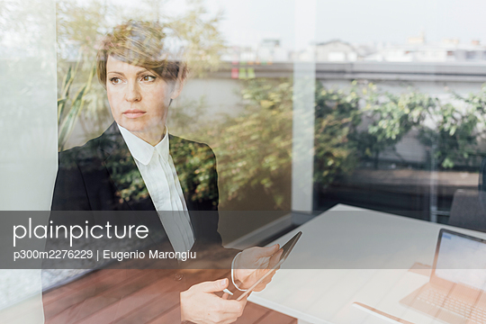 Serious businesswoman holding mobile phone while looking through window in office - p300m2276229 by Eugenio Marongiu