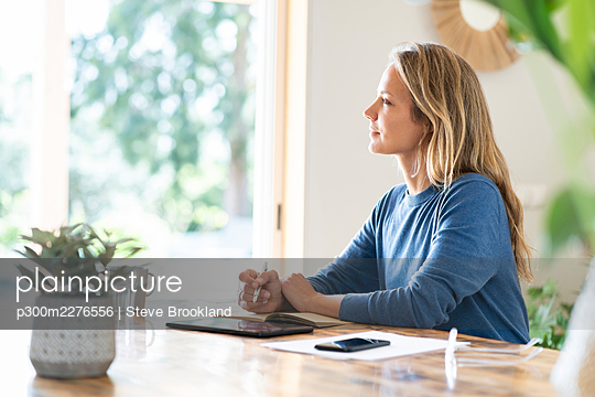 Blond businesswoman writing in diary while sitting at table - p300m2276556 by Steve Brookland