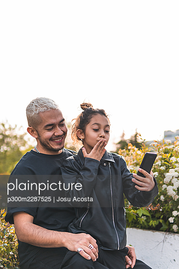 Girl taking selfie with father through smart phone at park - p300m2287525 by Josu Acosta