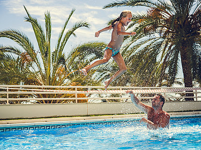 Father and daughter playing in the pool - p1084m986881 by Operation XZ