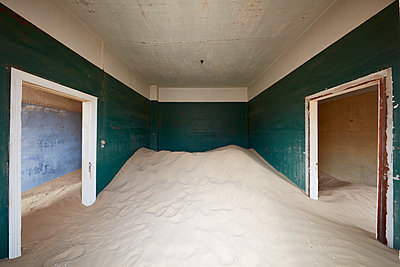 A deserted building, a room with painted walls and two doorways, and a heap of sand engulfing half the room.  - p1100m1489989 by Mint Images