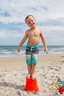 Portrait of playful boy standing on bucket at beach against cloudy sky - p1166m1542158 by Cavan Social