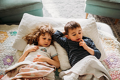 Brother and sister laying in livingroom together watching movie - p1166m2201212 by Cavan Images