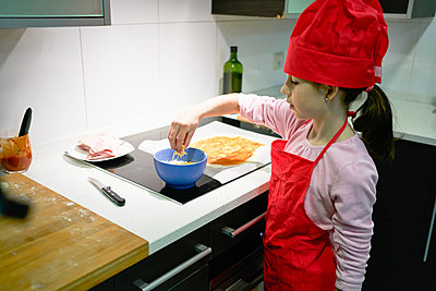 The girl with the red chef's hat adds the cheese to the pizza dough - p1166m2201421 by Cavan Images