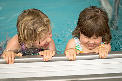 Two young girls in pool - p3720381 by James Godman