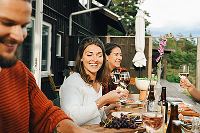Smiling woman looking at friend while enjoying during dinner in party - p426m2149268 by Maskot