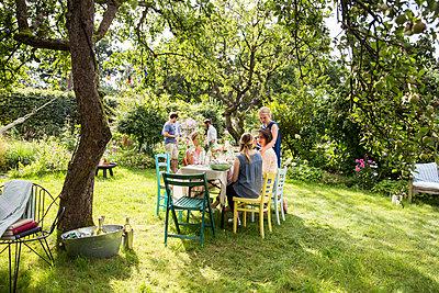 Friends having a garden party - p788m1165344 by Lisa Krechting