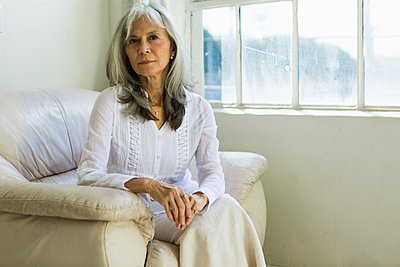 Portrait of senior woman sitting in apartment - p924m895707f by Luc-Richard Photography