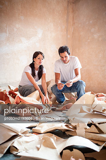 Young couple sits among wallpaper remains - p1093m2193604 by Sven Hagolani