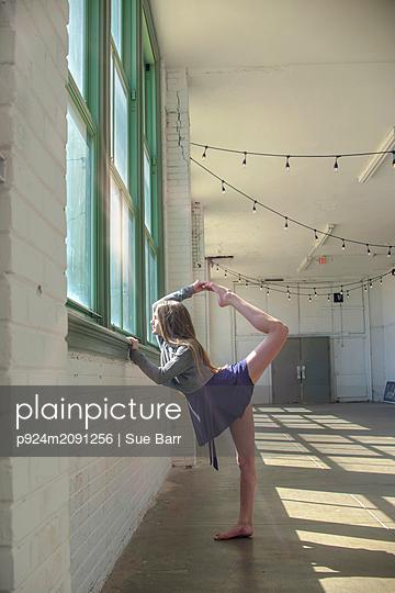 Teenage girl looking through dance studio window poised, holding raised leg - p924m2091256 by Sue Barr