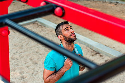 Top view of a bearded brunette athlete with towel around his neck on calisthenics bars. Outdoor fitness concept. - p1166m2268424 by Cavan Images
