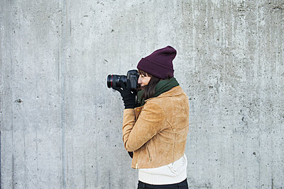 Woman wearing jacket photographing against wall - p1264m1122157f by Astrakan