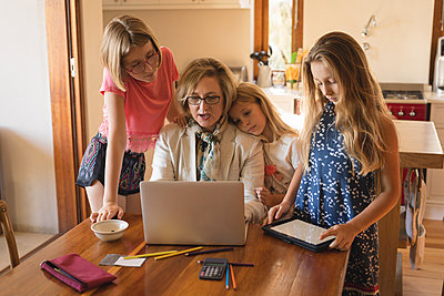 Mother and daughters using laptop and digital tablet - p1315m1579133 by Wavebreak