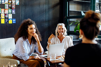 Businesswomen with laptop working together in loft office - p300m2144820 by Sofie Delauw