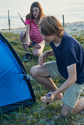 Young couple putting tent up - p312m1522227 by Johan Alp