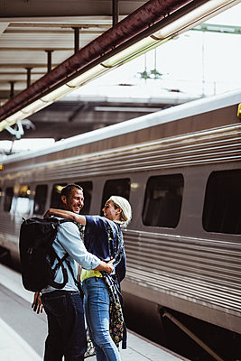 Happy couple embracing by train at railroad station - p426m2146044 by Maskot