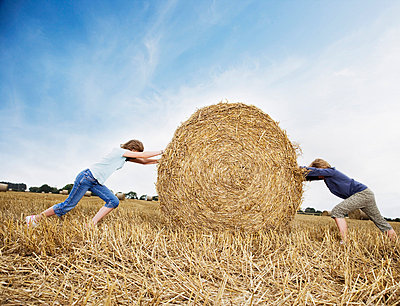 Two girls pushing against bale of hay - p6417819f by Anthony Lee