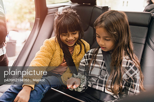 Sisters using digital tablet while sitting in electric car - p426m2194953 by Maskot