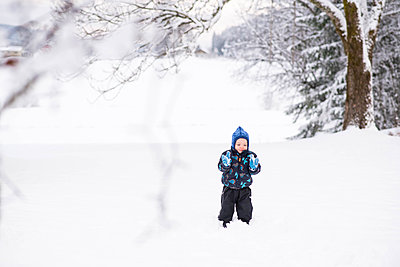 Boy kid child playing with snow in cold winter wonderland - p1166m2096362 by Cavan Images